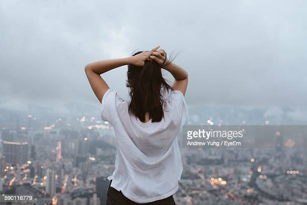 Rear View Of Woman Standing In Front Of Cityscape Against Sky During Foggy Weather