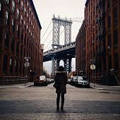Rear View Of Woman Standing In Front Of Manhattan Bridge
