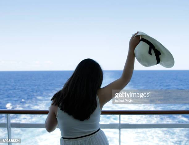 Rear View Of Woman Standing On Cruise Ship During Sunset