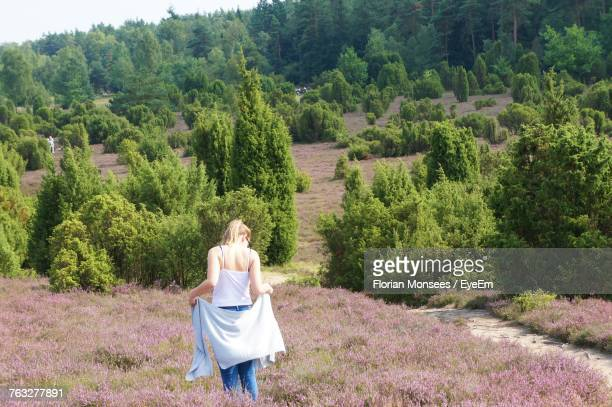 Rear View Of Woman Standing On Field During Sunny Day