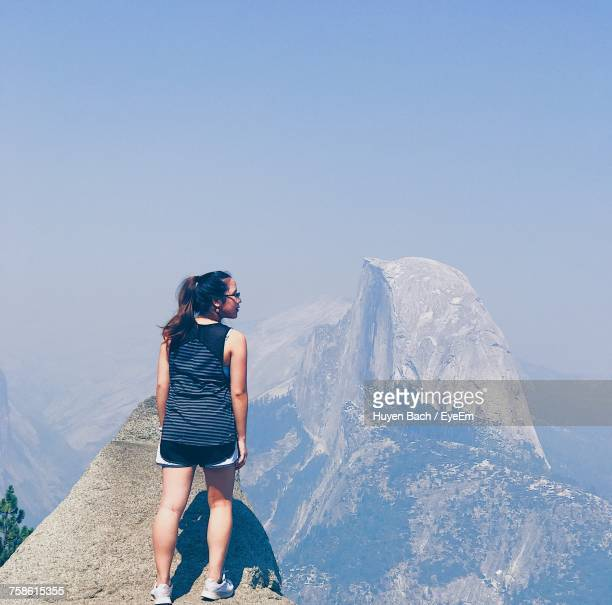 Rear View Of Woman Standing On Mountain Peak With Half Dome In Yosemite National Park Against Sky