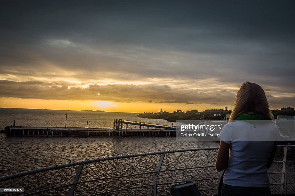 Rear View Of Woman Standing On Observation Point By Sea Against Sky During Sunset