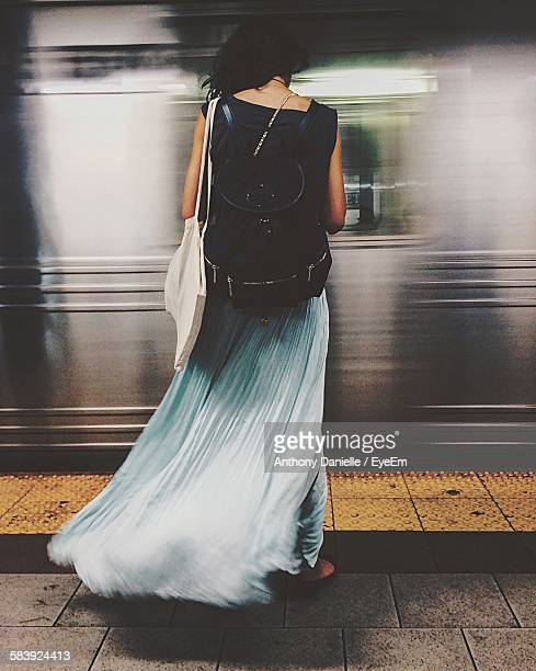 Rear View Of Woman Standing On Railroad Station Platform Against Moving Train