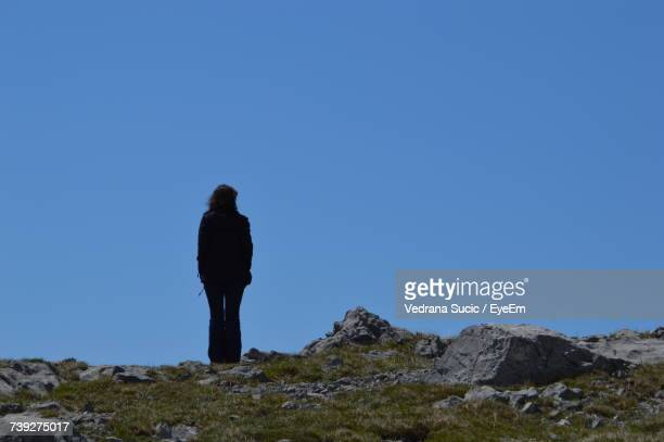 Rear View Of Woman Standing On Rock Against Clear Blue Sky