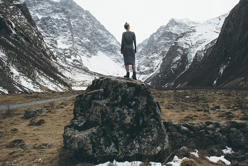 Rear view of woman standing on rock, North Ossetia, Russia