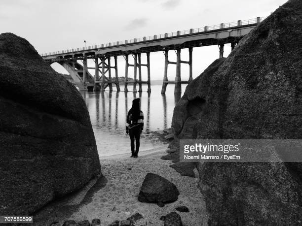 Rear View Of Woman Standing On Shore Against Bridge