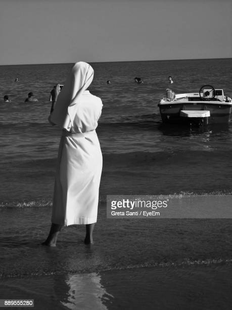 Rear View Of Woman Standing On Shore At Beach Against Clear Sky