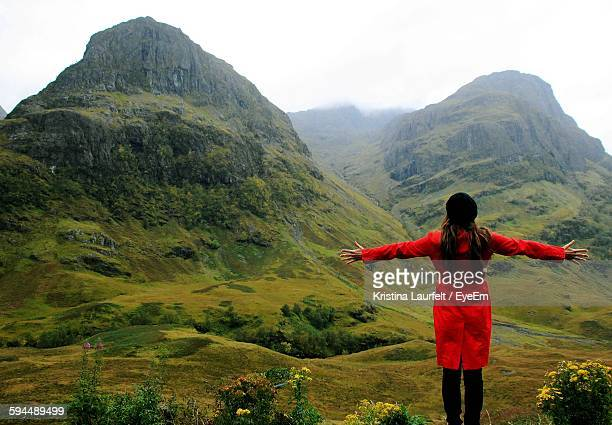Rear View Of Woman Standing With Arms Outstretched On Green Landscape