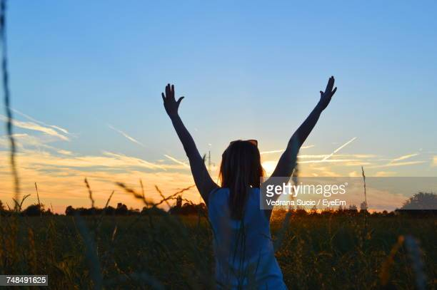 Rear View Of Woman Standing With Arms Raised On Field During Sunset