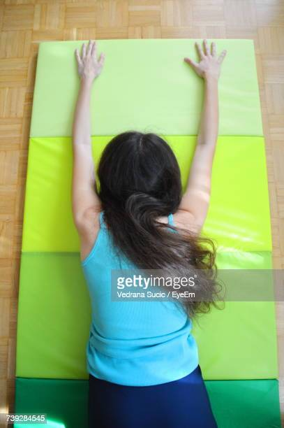 Rear View Of Woman Stretching On Exercise Mat