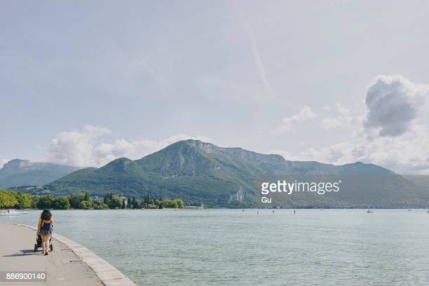 Rear view of woman strolling with pushchair waterfront at Lake Annecy, Annecy, Auvergne-Rhone-Alpes, France