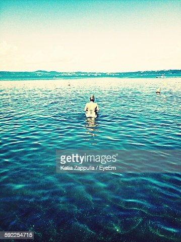 Rear View Of Woman Swimming In Lake Against Sky
