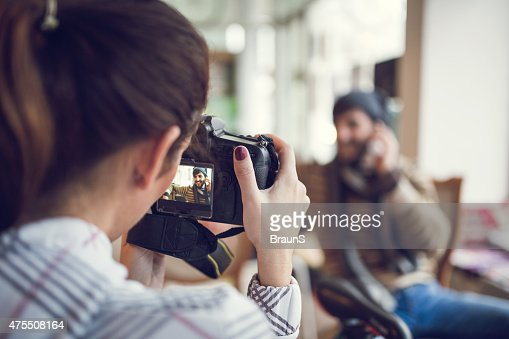 Rear view of woman taking a photo with digital camera.