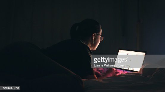 Rear View Of Woman Using Laptop On Bed
