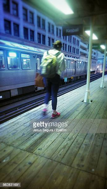 Rear View Of Woman Waiting Of Train At Station