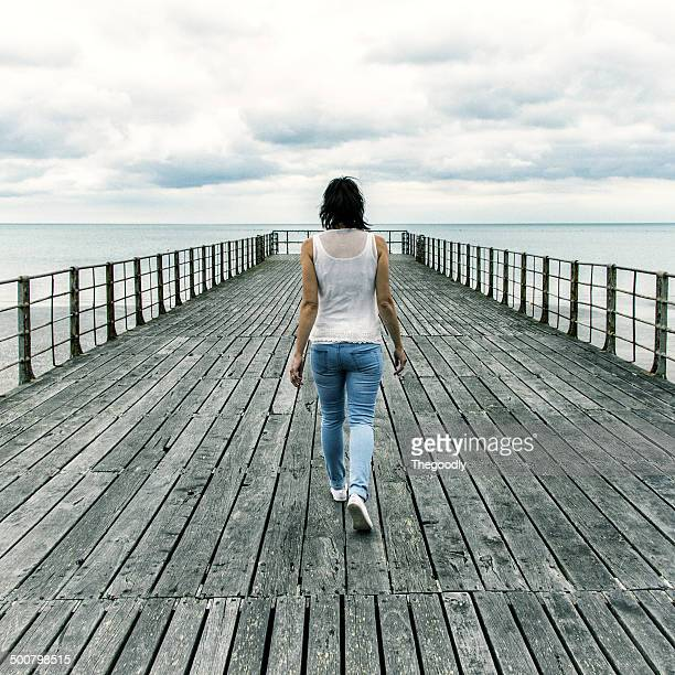 Rear view of woman walking along pier, England, UK