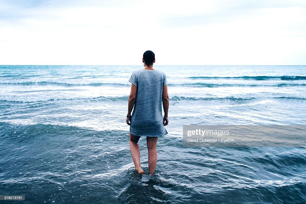 Rear View Of Woman Walking In Shallow Water At Beach