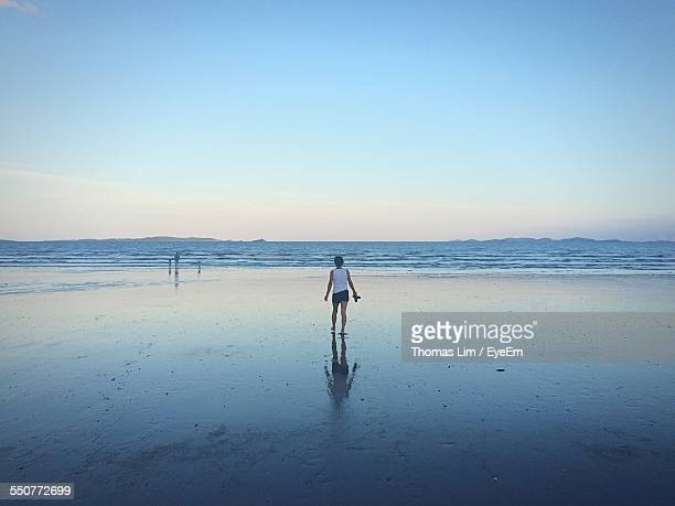 Rear View Of Woman Walking On Beach Against Sky