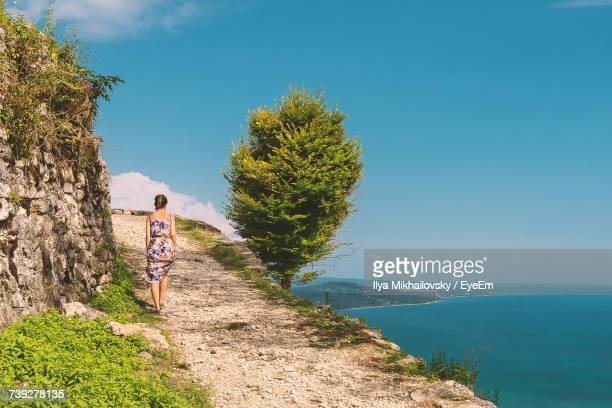 Rear View Of Woman Walking On Cliff Against Blue Sky