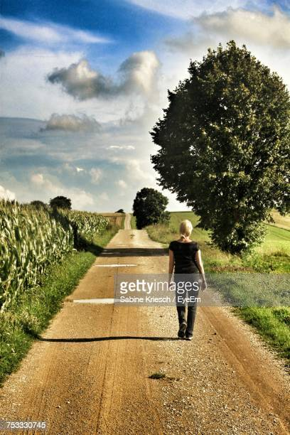 Rear View Of Woman Walking On Footpath Amidst Grassy Field During Sunny Day
