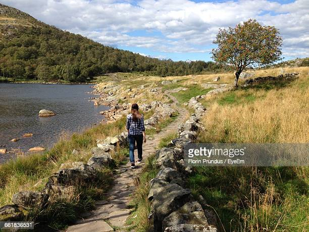Rear View Of Woman Walking On Footpath By River