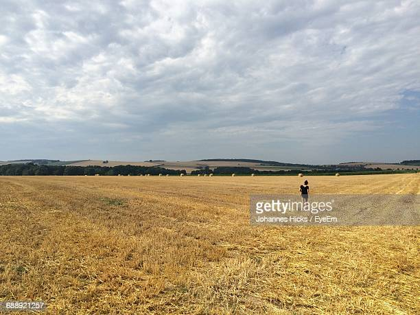 Rear View Of Woman Walking On Grassy Field Against Cloudy Sky