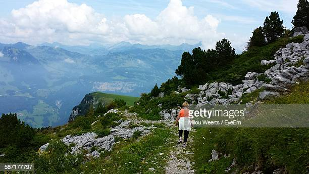 Rear View Of Woman Walking On Mountain Against Sky