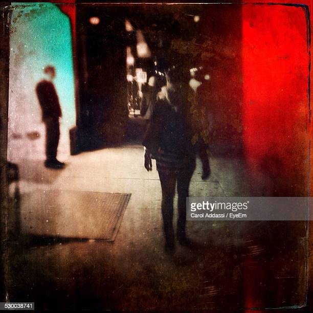 Rear View Of Woman Walking On Pathway At Night