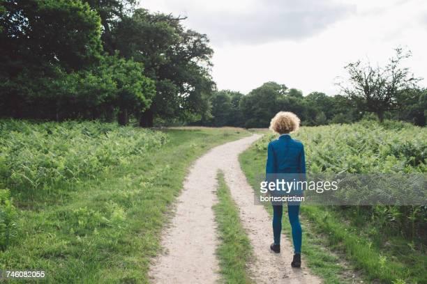 Rear View Of Woman Walking On Road Amidst Field