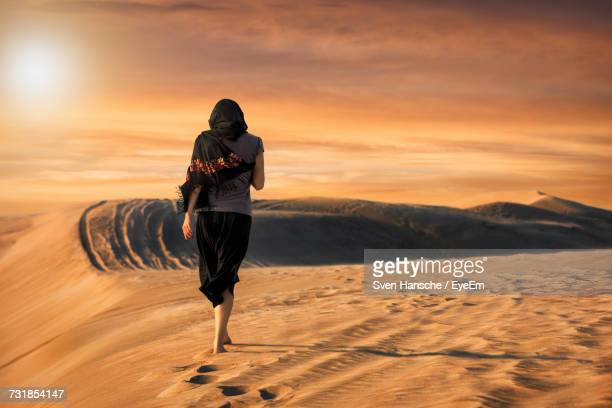 Rear View Of Woman Walking On Sand At Desert Against Sky During Sunset