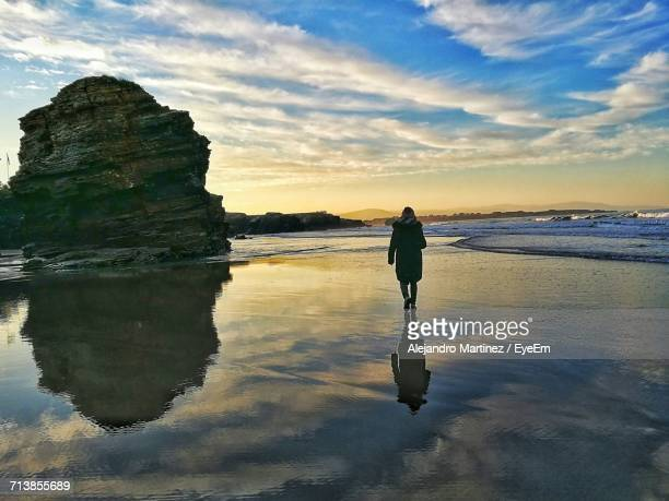 Rear View Of Woman Walking On Shore Against Cloudy Sky