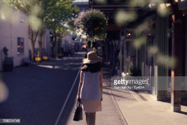 Rear View Of Woman Walking On Sidewalk During Sunny Day