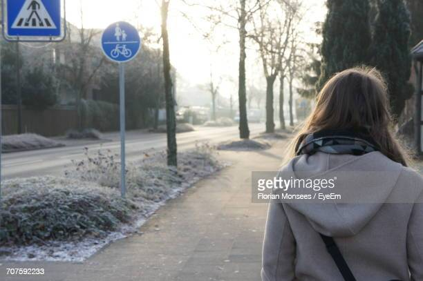 Rear View Of Woman Walking On Street During Winter