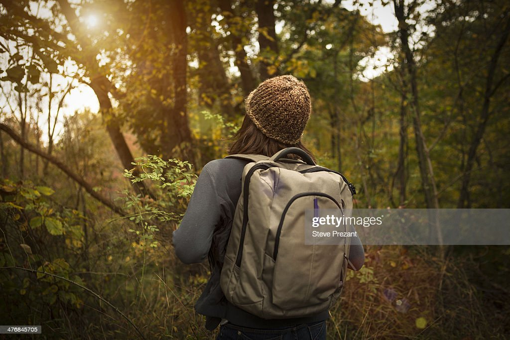 Rear view of woman walking through forest, carrying rucksack
