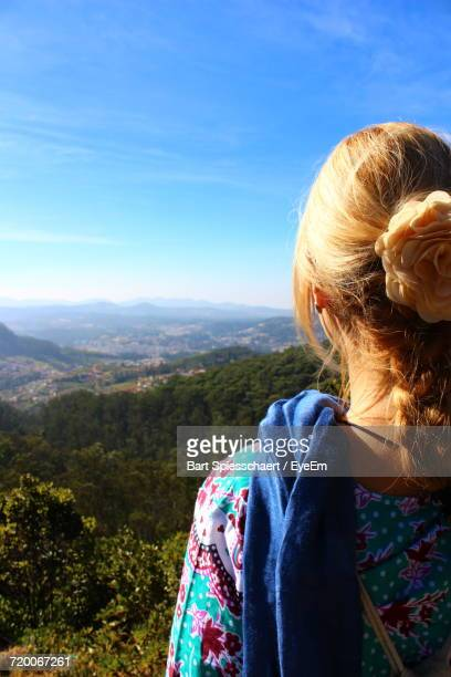 Rear View Of Woman Wearing Flower Looking At Mountains Against Sky