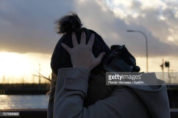 Rear View Of Woman Wearing Knit Hat Against Cloudy Sky During Sunset