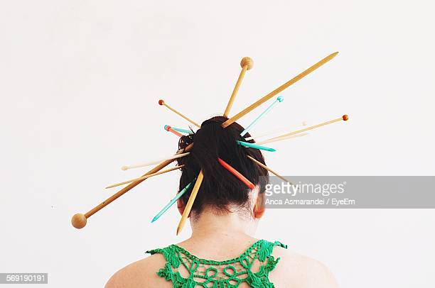 Rear view of woman wearing knitting needles against white background