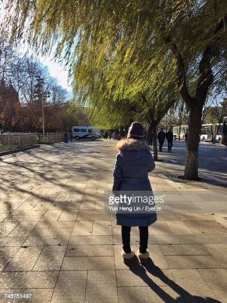 Rear View Of Woman Wearing Warm Clothing Standing On Footpath By Tree On Sunny Day