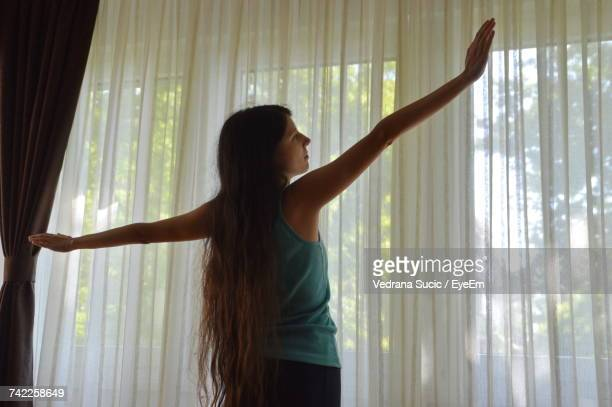 Rear View Of Woman With Arms Outstretched Standing Against Curtain At Home