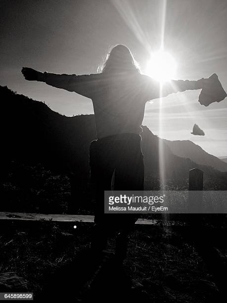 Rear View Of Woman With Arms Outstretched Standing On Field