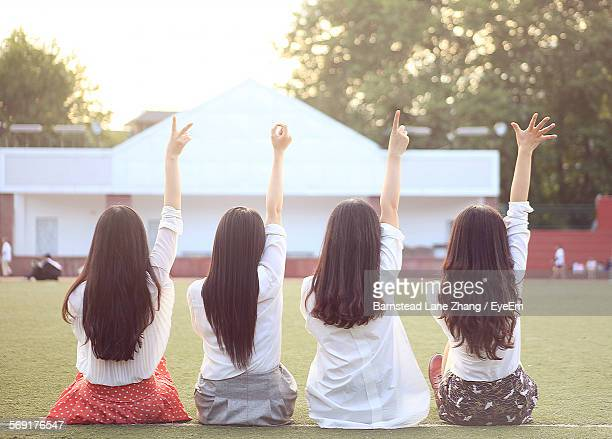 Rear View Of Woman With Arms Raised Gesturing In Lawn