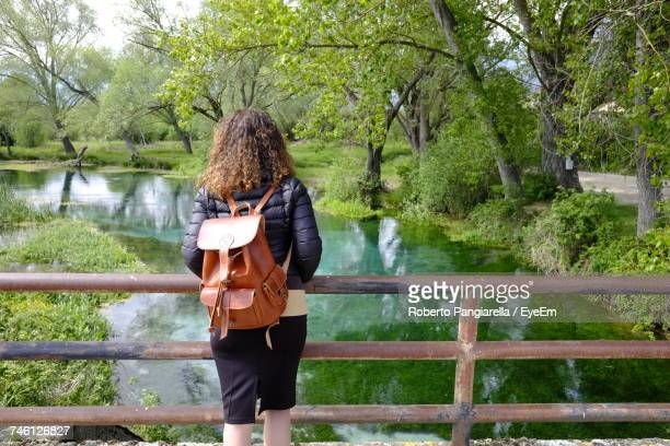 Rear View Of Woman With Backpack Standing On Footbridge Over River Against Trees