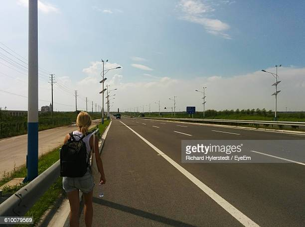 Rear View Of Woman With Bagpack Walking On Road Against Sky During Sunny Day