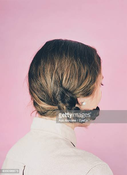 Rear View Of Woman With Braided Hair Around Face Against Pink Wall