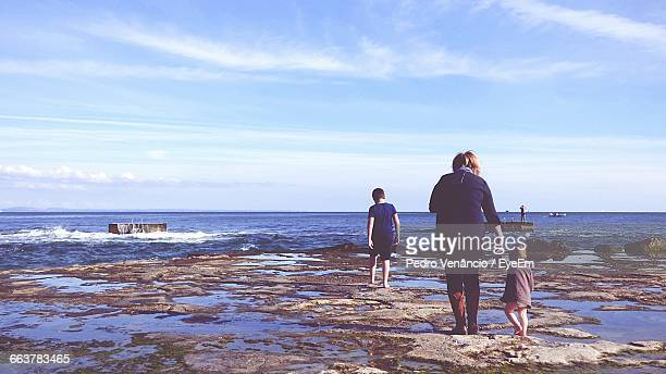 Rear View Of Woman With Daughter And Son At Beach