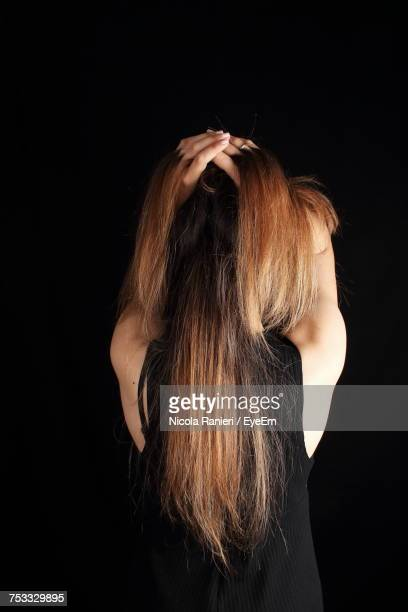 Rear View Of Woman With Hands In Hair Standing Against Black Background