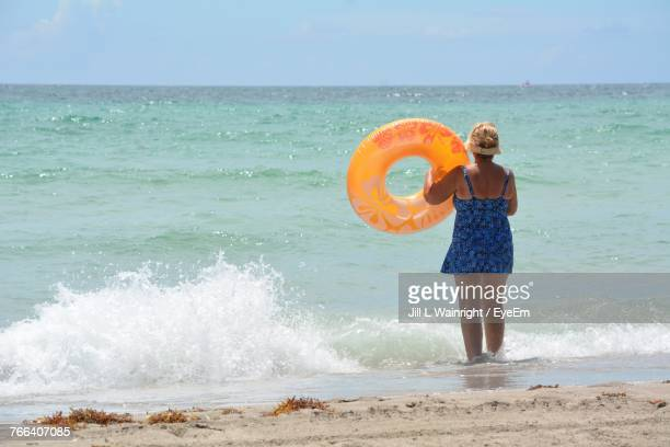 Rear View Of Woman With Inflatable Ring Walking At Beach Against Sky During Sunny Day