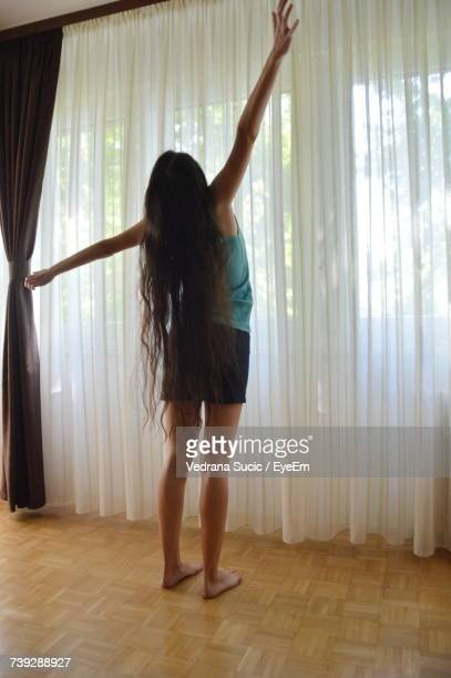 Rear View Of Woman With Long Hair Stretching While Standing Against Curtain At Home