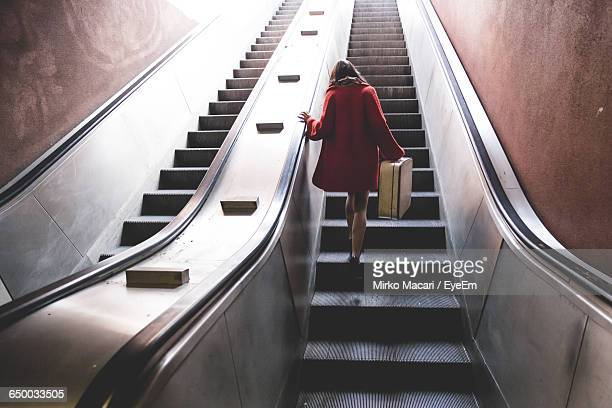 Rear View Of Woman With Luggage On Escalator In Subway