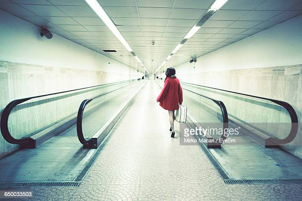 Rear View Of Woman With Luggage Walking On Pathway Amidst Moving Walkway In Illuminated Subway